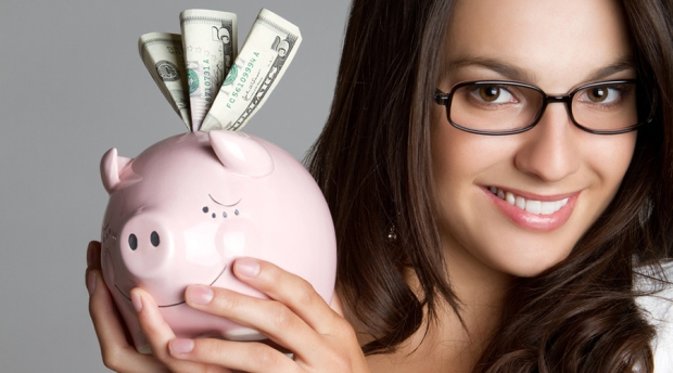 Smiling girl holding piggy bank money